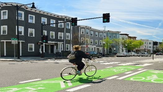 woman riding green bike lane